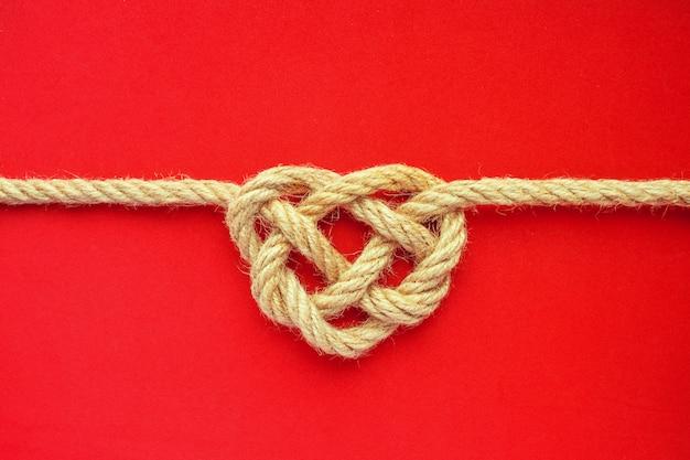 De kabelknoop van de hartvorm op rode achtergrond. jutekabel keltische knoop. hou van concept.