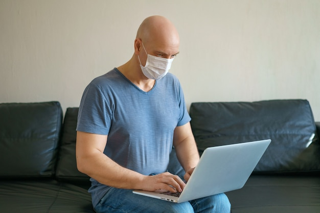 De kale mens werkt thuis aan laptop op een bank die een masker dragen tijdens quarantaine