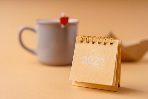 De kalender 2021 staat op een beige tafel tegen de achtergrond van een mok en een papieren bootje