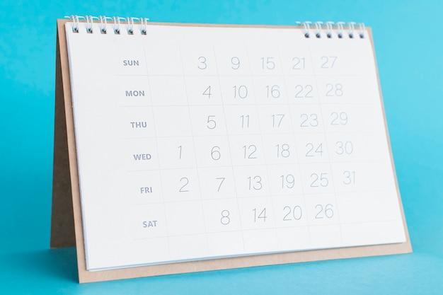 De kalender van de vooraanzichtkantoorbehoeften op blauwe achtergrond