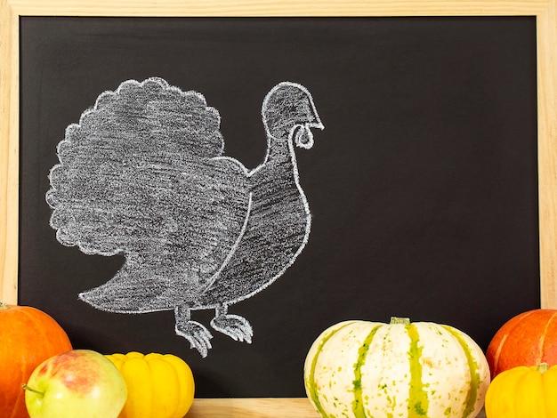 De kalkoen is getekend op een zwart bord. fijne thanksgiving-groeten. vrolijke thanksgiving. herfstoogst in een tijd van overvloed. gefeliciteerd met de seizoenen