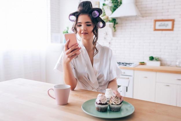 De kalme vreedzame jonge vrouw bekijkt in hand telefoon. kopje drank met pannenkoeken op plaat op tafel. alleen in de keuken. huishoudster met krulspelden in haar leeft onzorgvuldig leven.