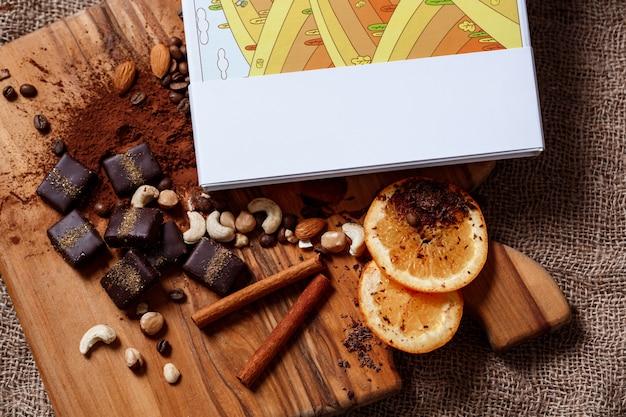 De kaneelsinaasappel en noten van het chocoladesuikergoed op houten bureau.