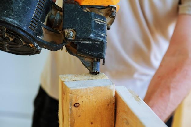 De kanonbouw schiet de spijkers de houten muur