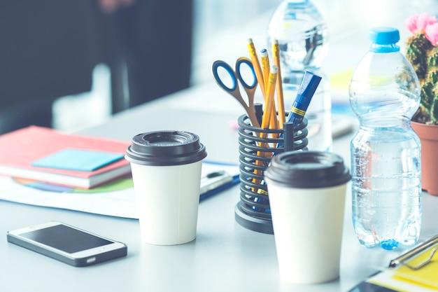 De kantoordesktop met een telefoon en een fles water
