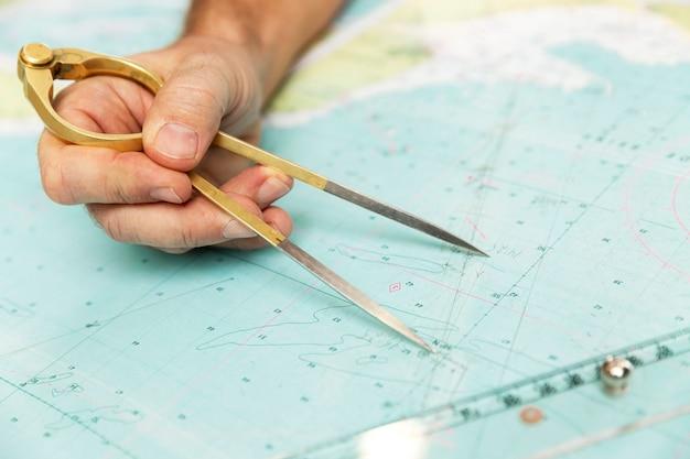 De kapitein meet de afstand op de kaart met een kompas. detailopname.