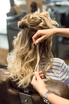 De kapper creëert krullen en golvend haar in de blonde. handen van de kapper krullen krullen bij de klant