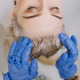 De kapper die van het gewassen haar het verfproces beëindigt