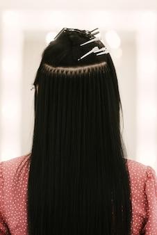 De kapper doet haarextensies aan een jong meisje in een schoonheidssalon. professionele haarverzorging. sluit omhoog van capsules en strengen van gegroeid haar