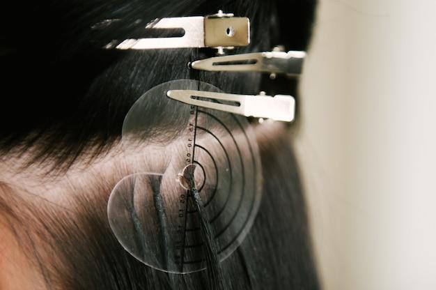 De kapper doet haarextensies aan een jong meisje in een schoonheidssalon. professionele haarverzorging.