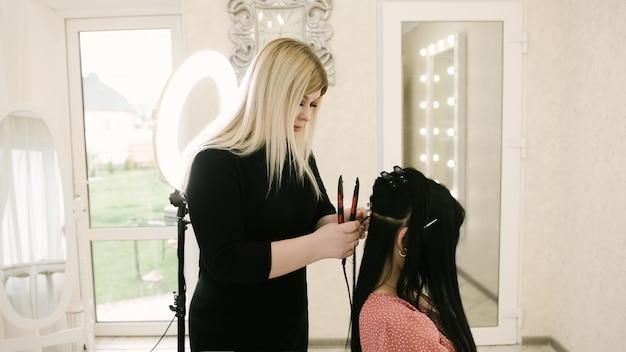 De kapper doet haarextensies aan een jonge vrouw in een schoonheidssalon