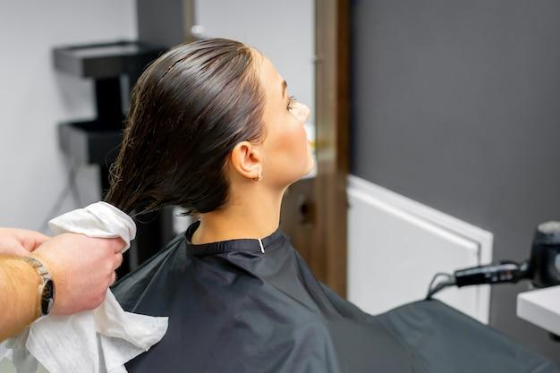 De kapper droogt het gewassen haar met een handdoek aan een mooie jonge brunette vrouw bij een schoonheidssalon