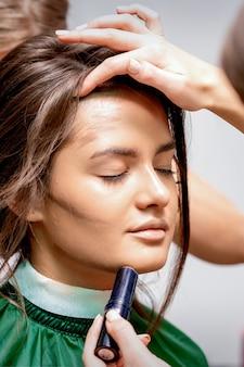 De kapper en visagist doen kapsel en make-up voor een mooie jonge blanke vrouw in een schoonheidssalon