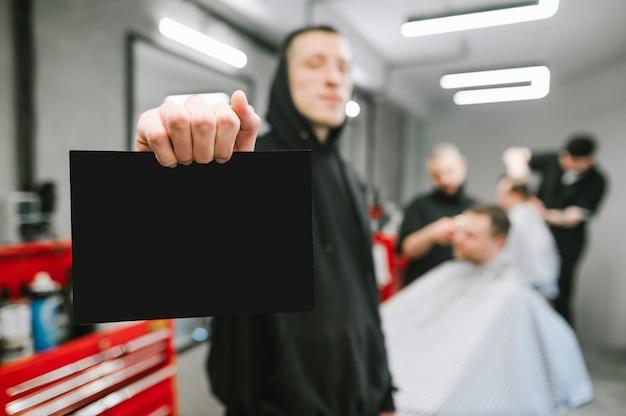 De kapper in zwarte hoodie houdt zwarte kaart op de achtergrond van de kapperswinkel en kappers die cliënten knippen. man houdt een blanco kaart in zijn hand op een achtergrond van een mannelijke kapper.