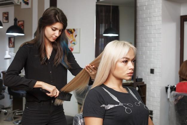 De kapper kamt het lange haar van de klant
