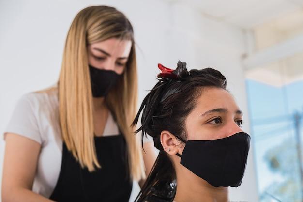 De kapper met zwarte handschoenen verft het haar van een vrouw - de kapper brengt kleurcrème op het haar aan.