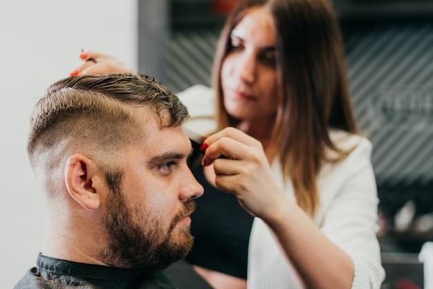 De kapper snijdt een bebaarde man met een schaar in de salon