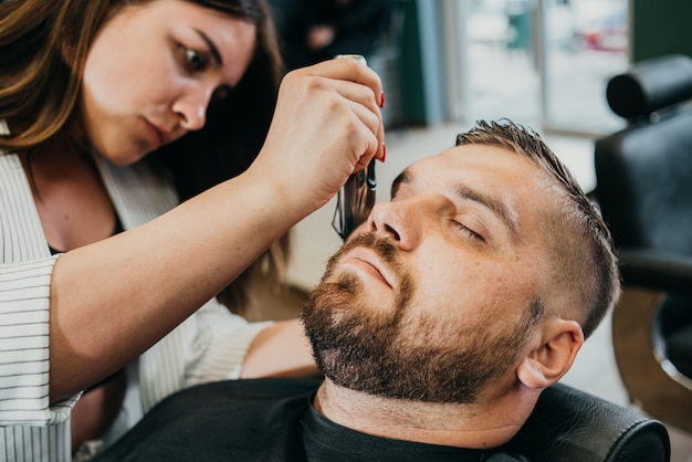 De kapper snijdt zijn baard aan een brutale man in de salon