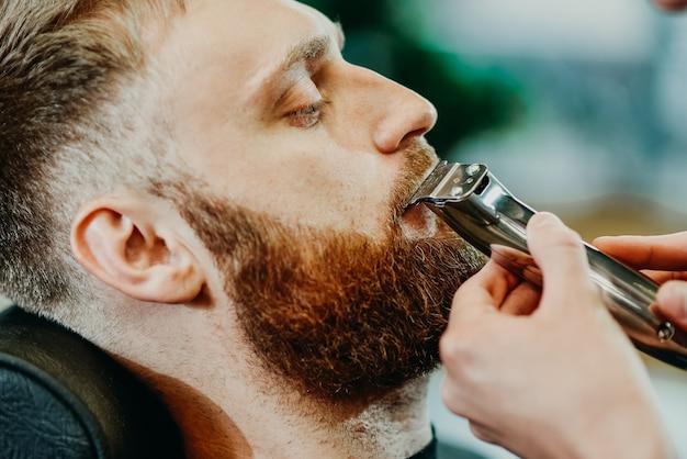 De kapper snijdt zijn baard aan een man in de salon
