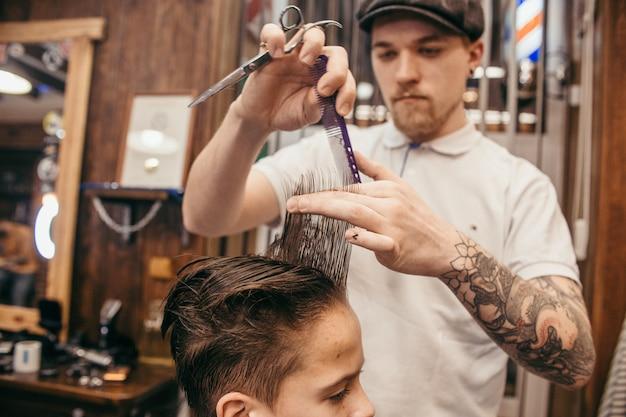 De kapper van tienerkapsels in de kapperswinkel. modieus stijlvol retro kapsel. portret