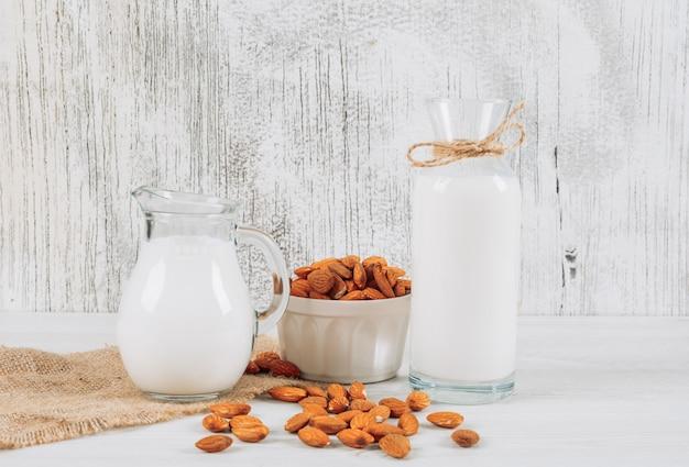 De karaf van de zijaanzichtmelk met kom van amandelen en fles melk op witte houten en stuk van zakachtergrond. horizontaal