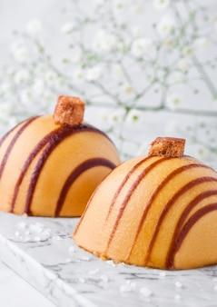 De karameldessert van het luxerestaurant op marmeren raad met bloemen