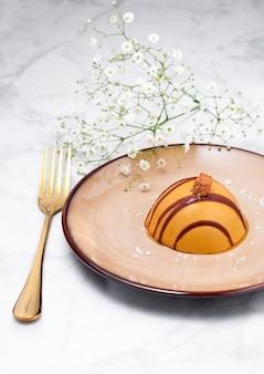 De karameldessert van het luxerestaurant op plaat met gouden vork en bloemen