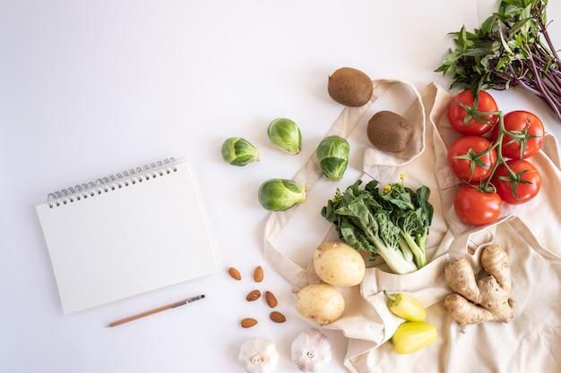 De katoenen zak van de ecototalisator met verse groenten op vlakte legt witte achtergrond. plastiek vrij voor het winkelen en de levering van het kruidenierswarenproduct. levensstijl zonder afval. gezonde voeding en veganistisch dieet.