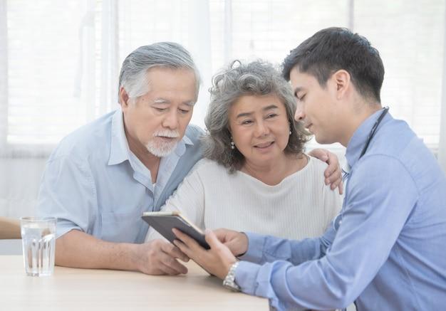De kaukasische arts gebruikt tablet en spreekt met oude aziatische vrouwelijke patiënt over ziektesymptoom