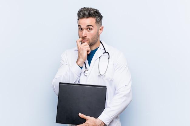 De kaukasische artsenmens die een omslag houdt ontspande het denken over iets bekijkend een exemplaarruimte.
