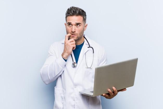De kaukasische artsenmens die laptop houden ontspande het denken over iets bekijkend een exemplaarruimte