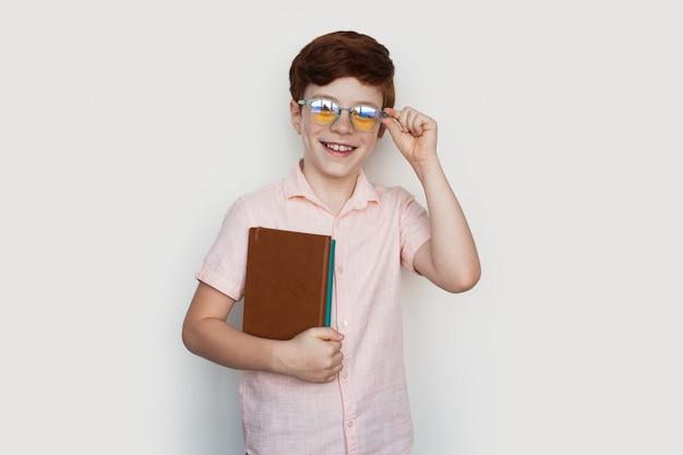 De kaukasische gemberjongen met bril glimlacht bij camera die enkele boeken op een witte studiomuur in vrijetijdskleding houdt