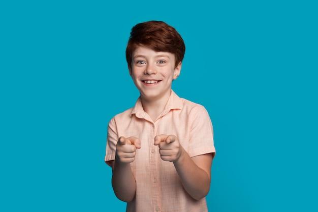 De kaukasische glimlachende jongen gebaart naar camera met vinger die op een blauwe studiomuur met vrije ruimte richt