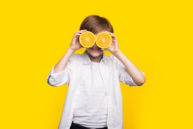 De kaukasische jongen behandelt zijn oog met gesneden citroenen die op een gele studiomuur glimlachen Premium Foto