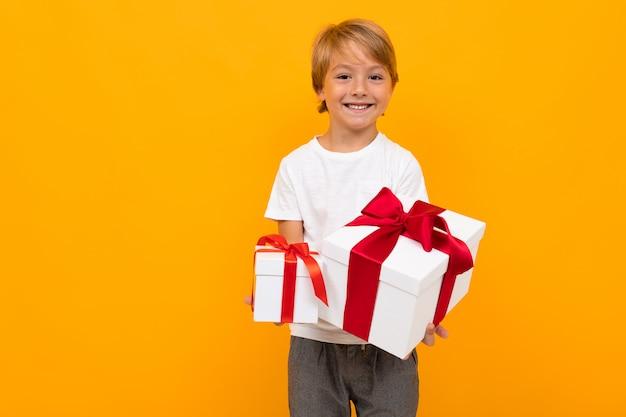 De kaukasische jongen houdt vele witte dozen met giften en verheugt zich, portret dat op gele muur wordt geïsoleerd