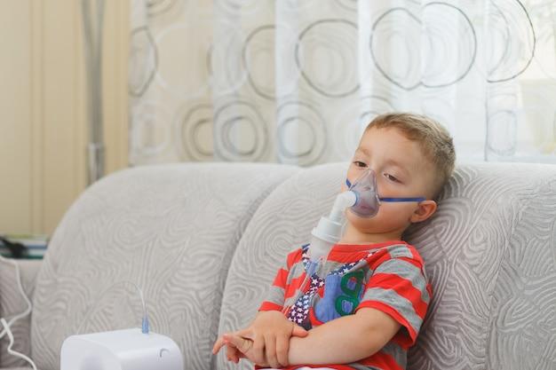 De kaukasische jongen inhaleert paren die medicijn bevatten om te stoppen met hoesten.