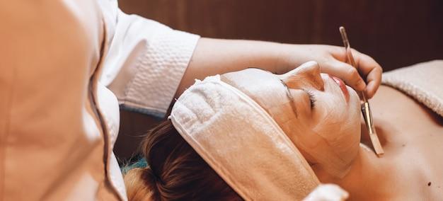 De kaukasische kuuroordmedewerker die een borstel gebruikt, brengt een huidverzorgingscrème aan op het gezicht en de hals van de cliënt