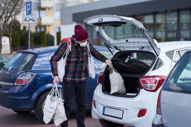 De kaukasische mens die medisch masker draagt, verpakt reusachtige hoeveelheid zakken met voedsel in auto na het winkelen tijdens uitbraak
