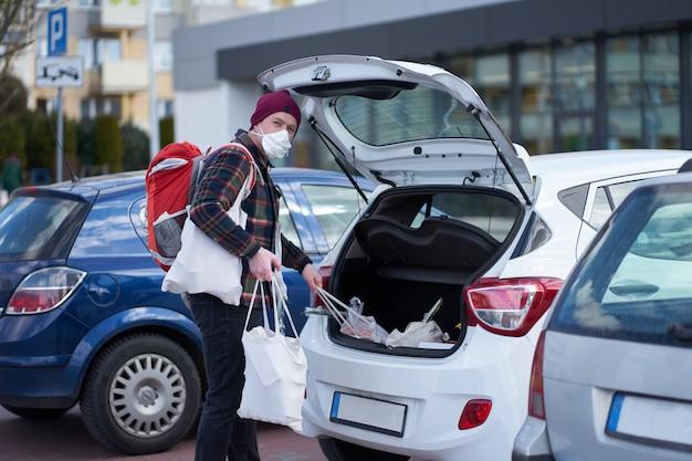 De kaukasische mens die medisch masker draagt, verpakt zakken in auto na het winkelen tijdens uitbraak