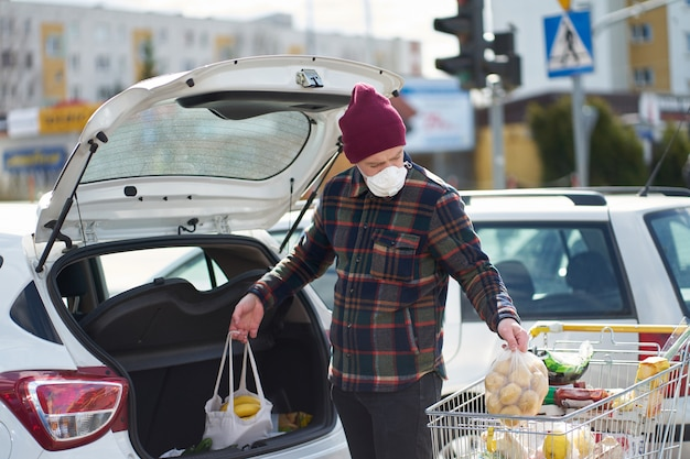 De kaukasische mens die medisch masker draagt, verpakt zakken met voedsel van kar in auto na het winkelen tijdens uitbraak