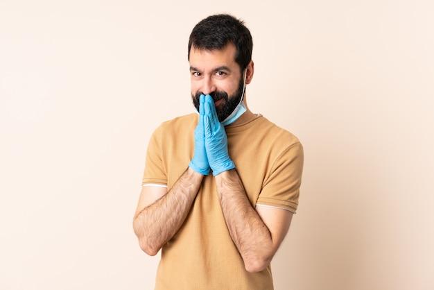 De kaukasische mens die met baard tegen het coronavirus beschermt met een masker en handschoenen over muur houdt palm samen.