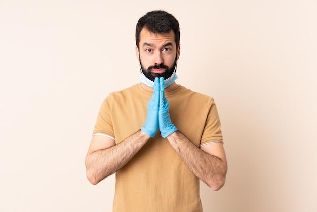 De kaukasische mens met baard die met een masker en handschoenen over geïsoleerde muur beschermt houdt palm samen. persoon vraagt iets