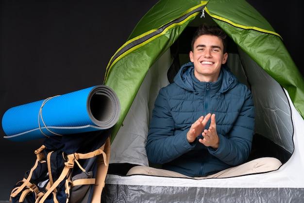 De kaukasische mens van de tiener binnen een het kamperen groene tent die bij het zwarte toejuichen na presentatie in een conferentie wordt geïsoleerd