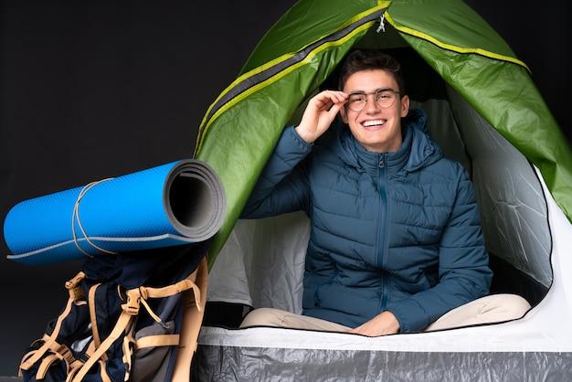 De kaukasische mens van de tiener binnen een het kamperen groene tent die op zwarte achtergrond met glazen wordt geïsoleerd en gelukkig