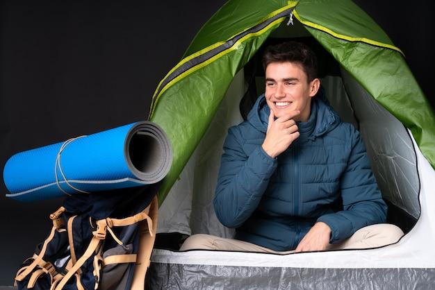 De kaukasische mens van de tiener binnen een het kamperen groene tent die op zwarte achtergrond wordt geïsoleerd die aan de kant kijkt