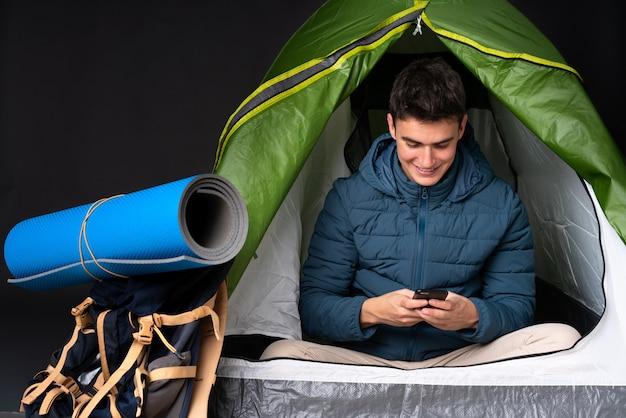 De kaukasische mens van de tiener binnen een het kamperen groene tent die op zwarte achtergrond wordt geïsoleerd die een bericht met mobiel verzendt