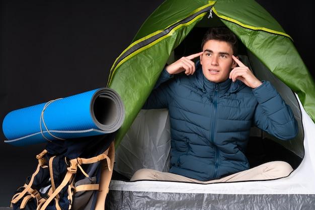De kaukasische mens van de tiener binnen een het kamperen groene tent die op zwarte achtergrond wordt geïsoleerd die twijfels en het denken heeft