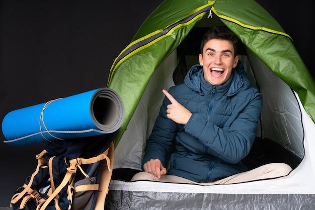De kaukasische mens van de tiener binnen een het kamperen groene tent die op zwarte verraste achtergrond wordt geïsoleerd en kant richt