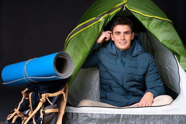 De kaukasische mens van de tiener binnen een het kamperen groene tent die op zwarte wordt geïsoleerd die twijfels heeft