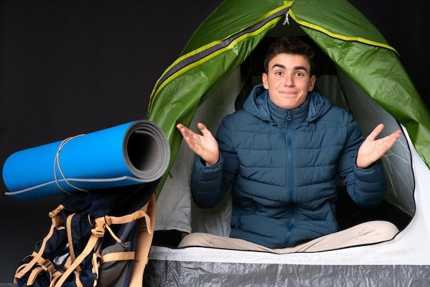 De kaukasische mens van de tiener binnen een het kamperen groene tent die op zwarte wordt geïsoleerd die twijfelsgebaar maakt